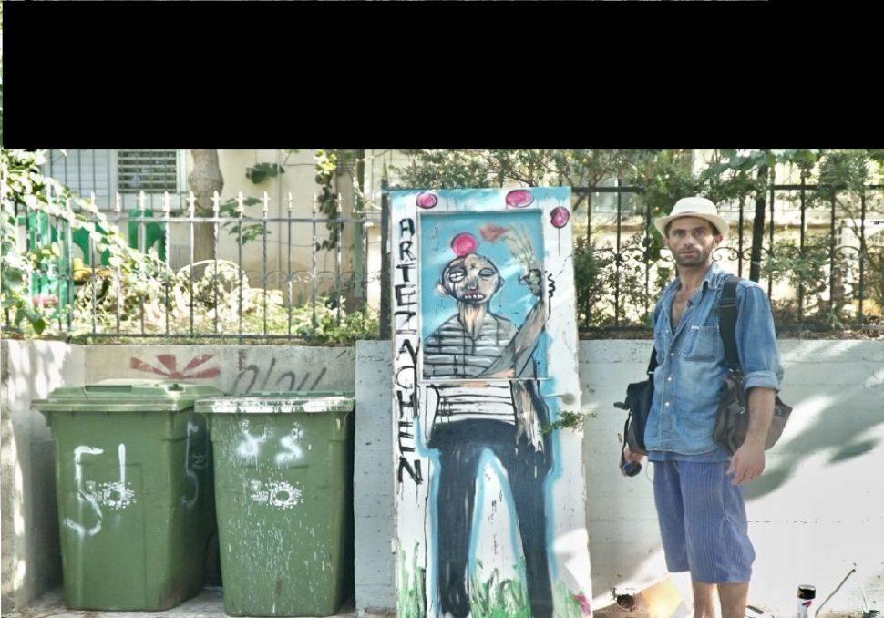 איש בחולצת ג'ינס ומצלמה ליד פחי זבל ירוקים