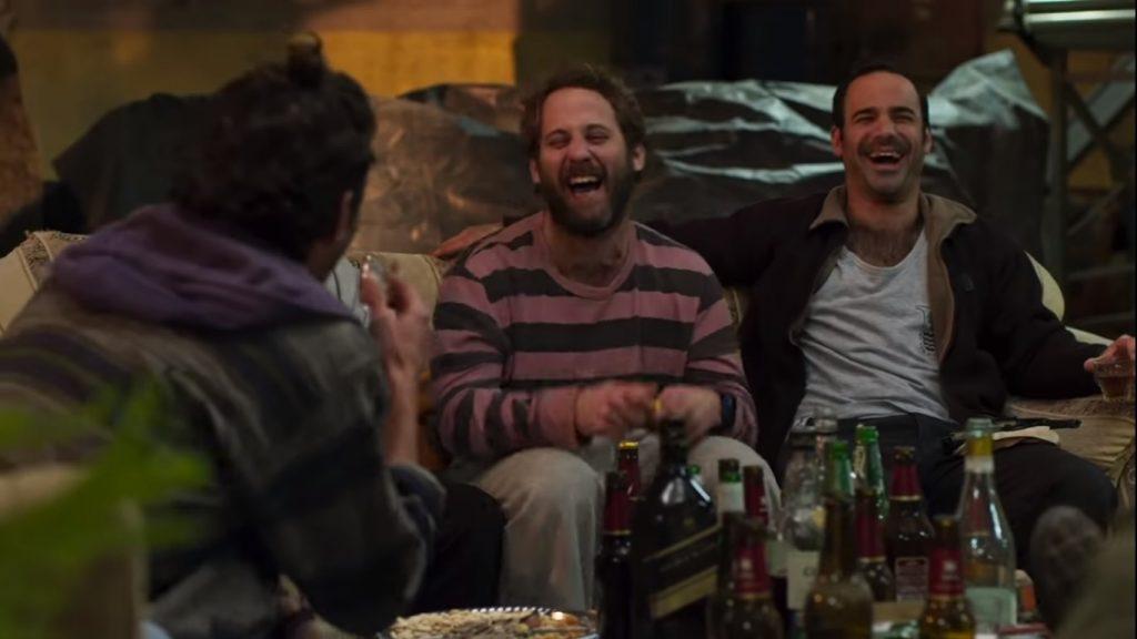 שני אנשים יושבים על ספה וצוחקים