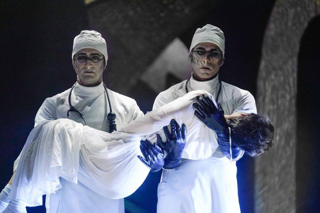 """סצנה מתוך ההצגה """"מתאבל ללא קץ"""". שני רופאים בבגדים לבנים נושאים ילד מת"""