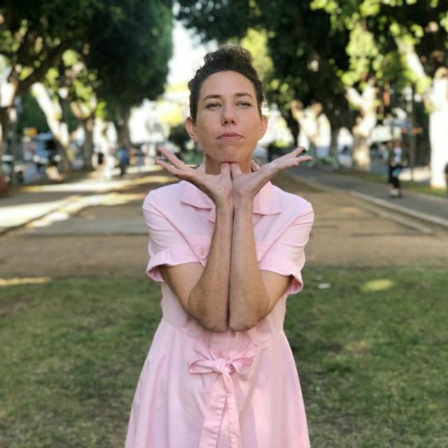 בחורה בשמלה ורודה על רקע שדרה