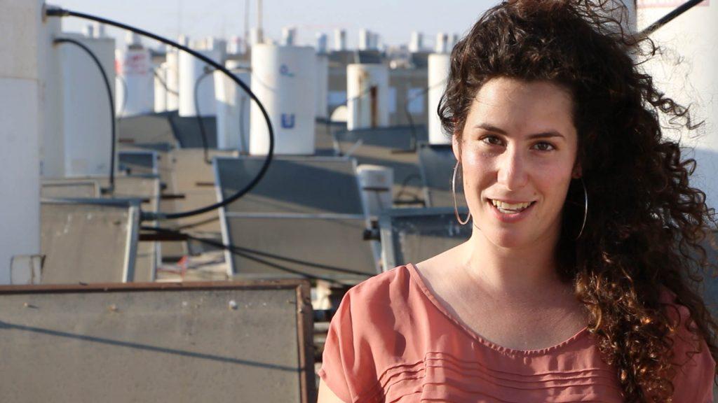 """יעל רומני, יזמת פסטיבל """"סרטים על שיכונים"""" על גג בניין עם קולטים ודודי שמש ברקע"""