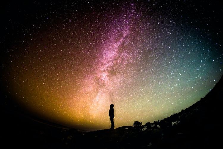 איש עומד מתחת לשמיים צבעוניים