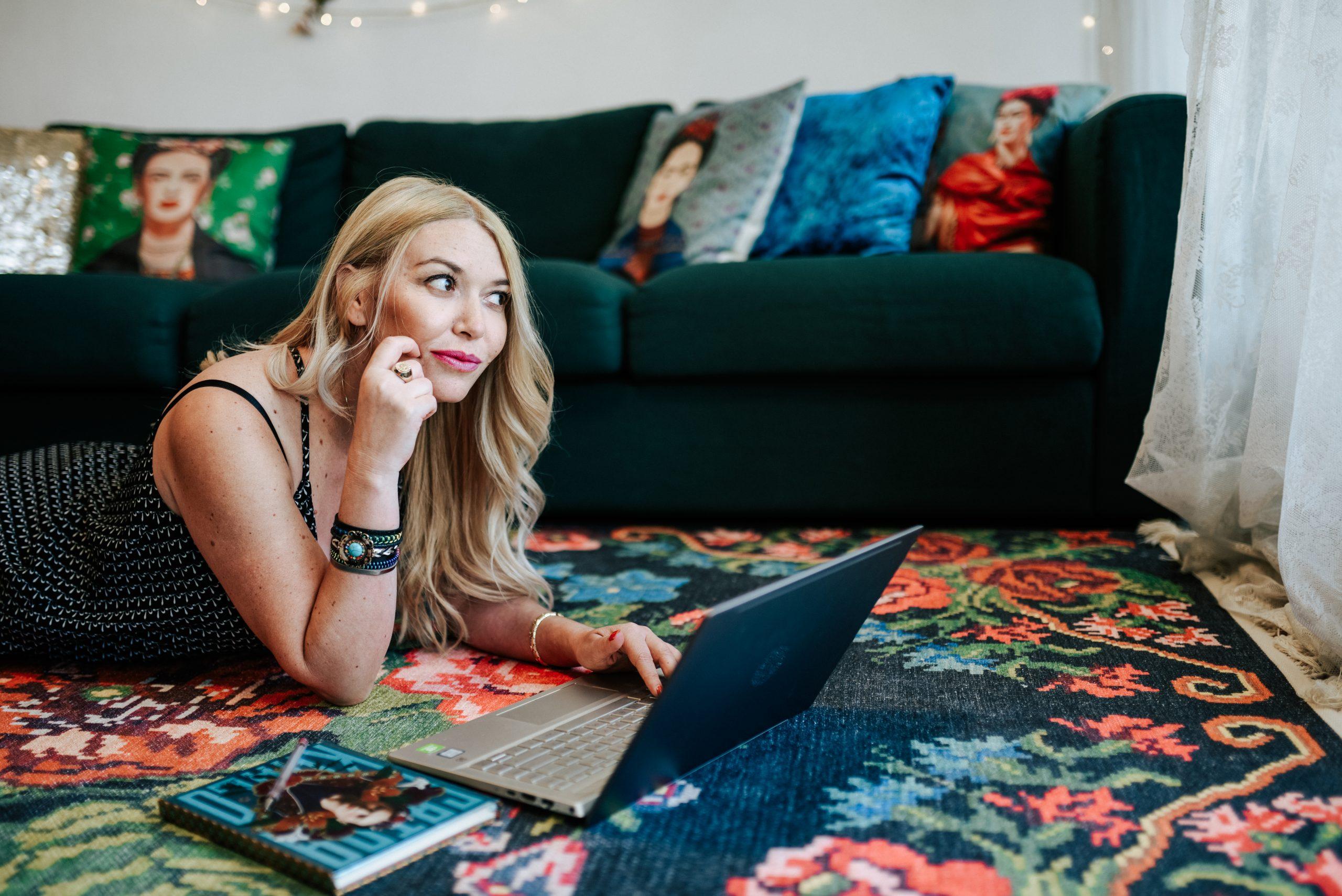 דנה לוי אלגרוד שוכבת על שטיח צבעוני ולידה מחשב נייד